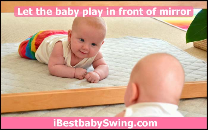baby playing in front of mirror