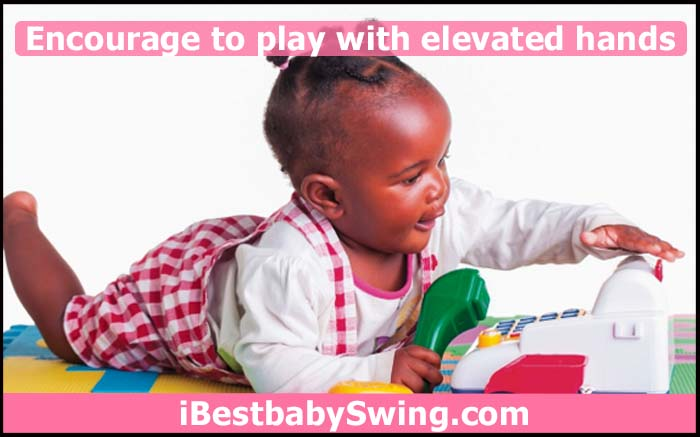 baby playing with toys with elevated hands
